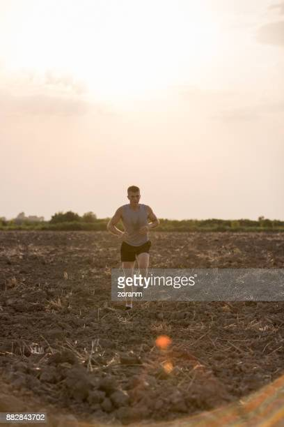 Young man jogging on dirth path at sunset