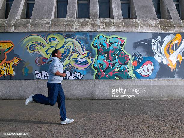 young man jogging past graffiti wall - graffiti foto e immagini stock