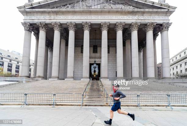 young man jogging past the new york county courthouse in foley square on centre street, new york city - bandana stock pictures, royalty-free photos & images