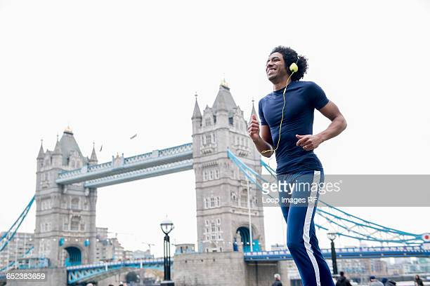 A young man jogging past Tower Bridge in London