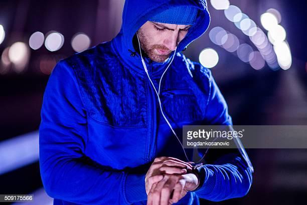 Young man jogging through the city at night