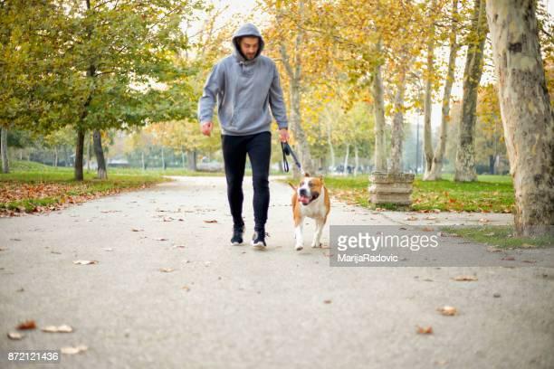 Jeune homme, faire du jogging avec son chien dans le parc