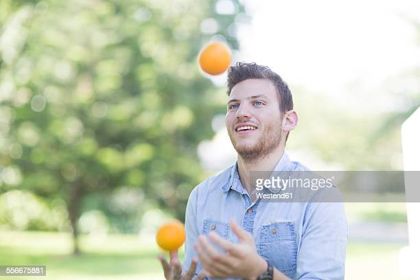 Young man juggling with oranges outdoors