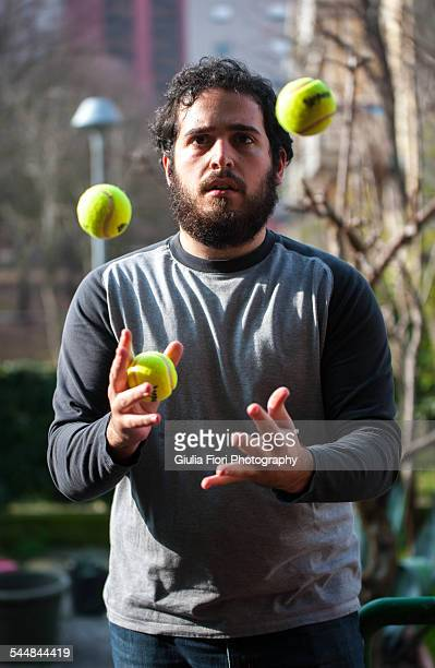 Young man juggling with tennis balls