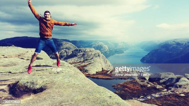 Young Man Jumping Against Cloudy Sky At Preikestolen