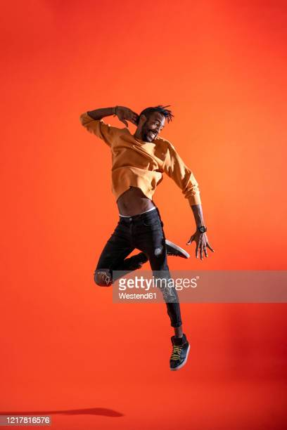young man jumping and dancing in front of orange wall - danseuse photos et images de collection