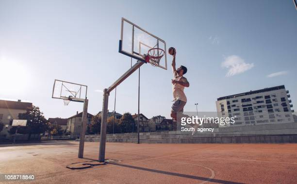 young man jumping and making a fantastic slam dunk - shooting baskets stock pictures, royalty-free photos & images
