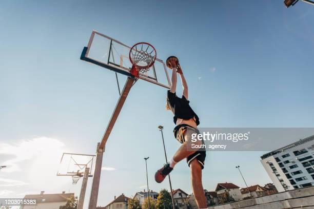 junger mann springt und macht einen fantastischen slam-dunk - basketball stock-fotos und bilder