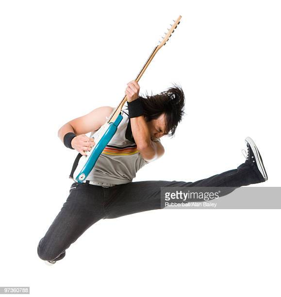 young man jumping and playing guitar, studio shot - パンクロック ストックフォトと画像