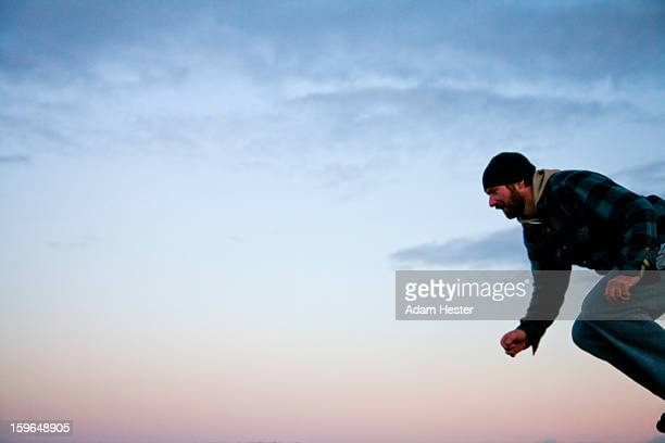 A young man jumping at sunset with a colorful sky.