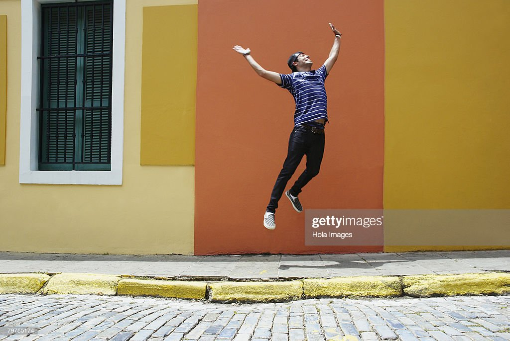 Young man jumping at the roadside : Stock Photo