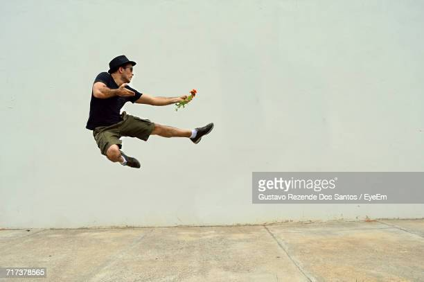 Young Man Jumping By Wall