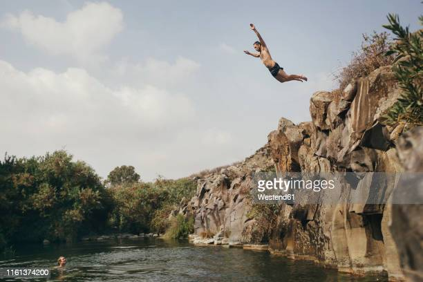 young man jumping from a cliff, yehudiya reserve, golan, israel - israel independence day stock pictures, royalty-free photos & images
