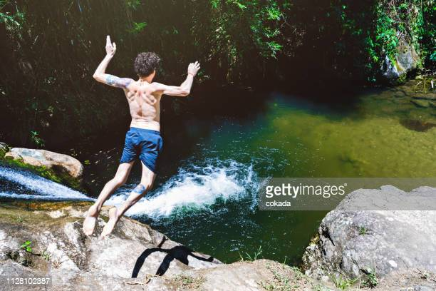 young man jumping from a waterfall at lumiar/rj - falling water stock photos and pictures