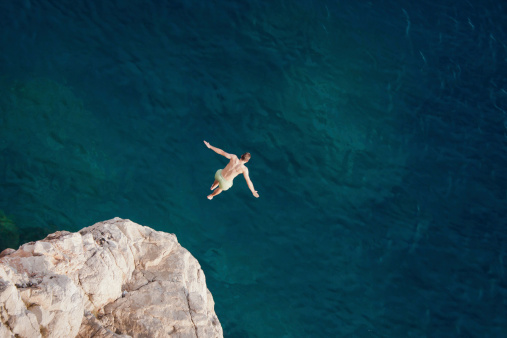 Young man jumping from cliff into sea. 465925131