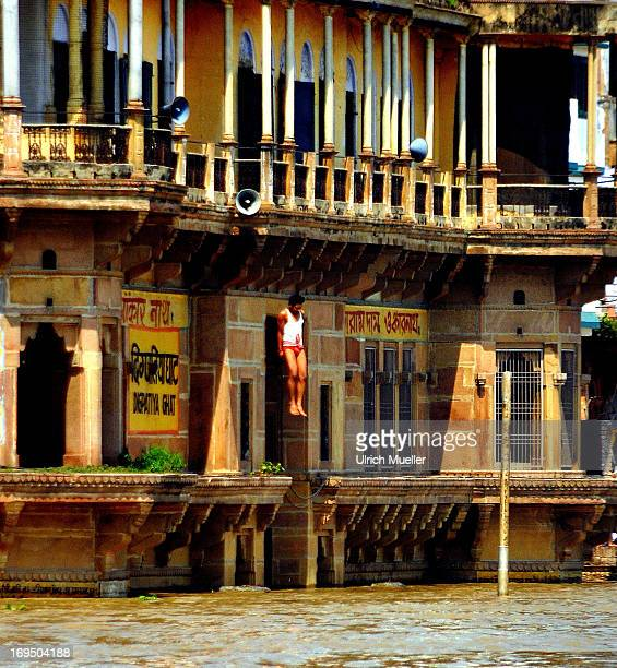 Young man jumping from the roof of a house in the River Ganges