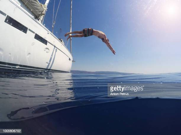 Young man jumping from the yacht into the water. Underwater photo