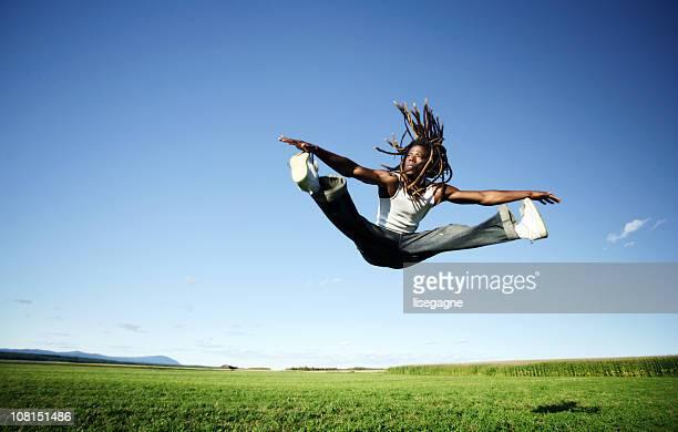 Jeune homme sautant en l'Air et en faisant diviser