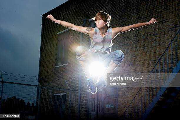 young man jumping in air on rooftop