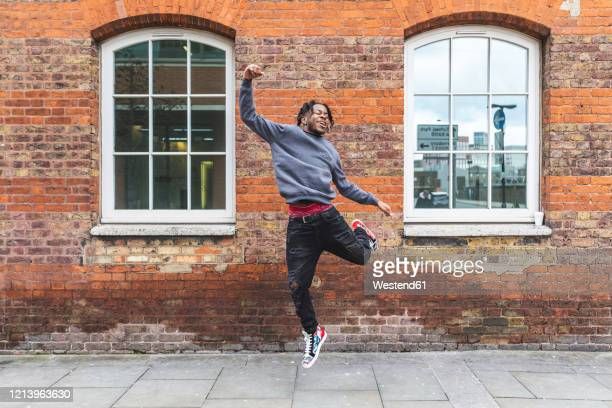 young man jumping in front of brick wall - jumping stock pictures, royalty-free photos & images