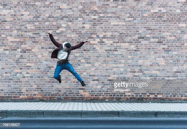 Young man jumping in front of brick wall