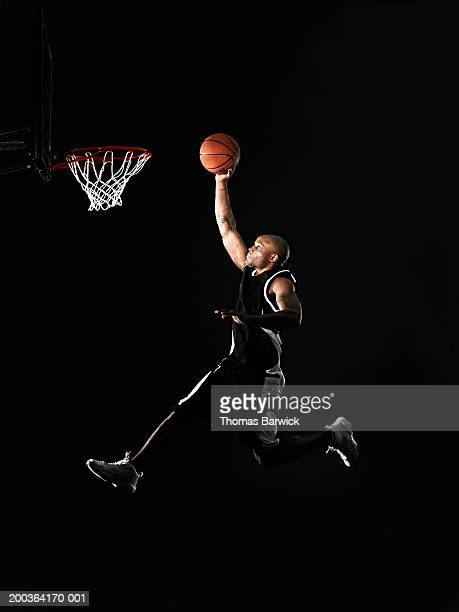 Young man jumping in mid air, preparing to dunk basketball, side view
