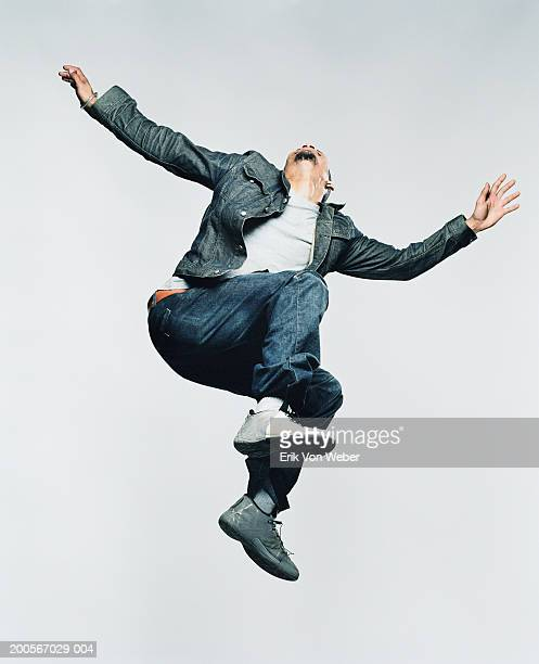 Young man jumping in mid-air, low angle view