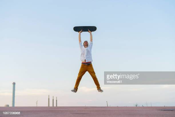 young man jumping in the air holding a skateboard - holding aloft stock pictures, royalty-free photos & images