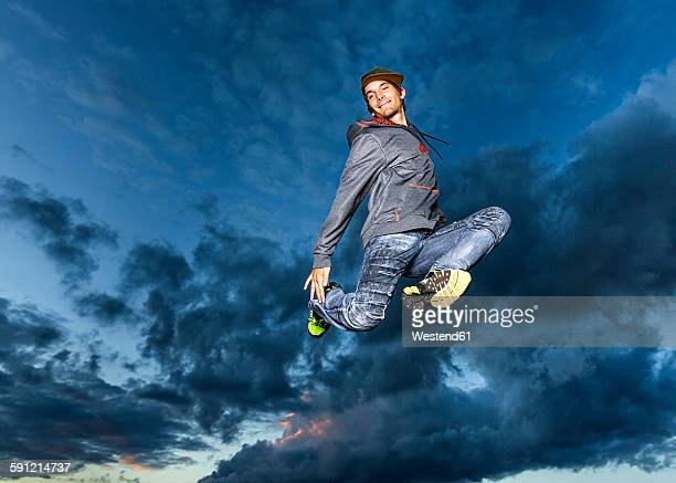 Young man jumping in the air in front of evening sky