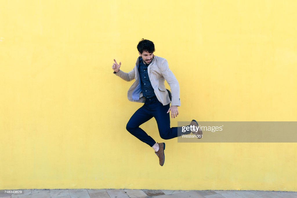 Young man jumping in the air in front of yellow wall : Stock-Foto