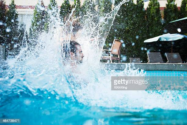 Young man jumping into a pool with water splashing all around him
