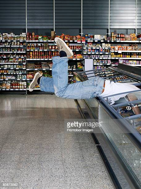 young man jumping into refrigerator.  - gier stock-fotos und bilder