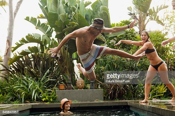 Young man jumping into swimming pool