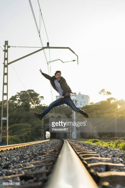 Young man jumping into the air, railroad track