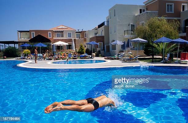 Junger Mann, Springen in den pool im Innenhof