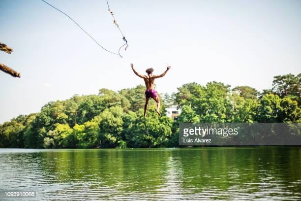 young man jumping into the lake - 25 29 años fotografías e imágenes de stock