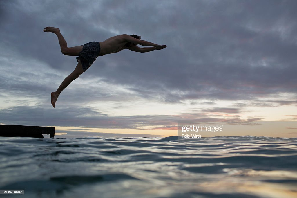 Young man jumping into water at sunset : Foto de stock