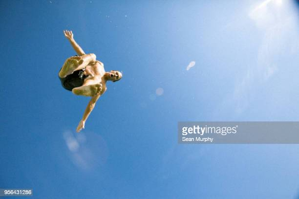 Young man jumping, mid air, low angle view