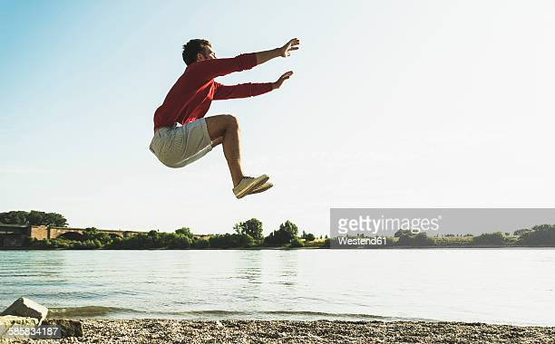 Young man jumping mid-air by the riverside
