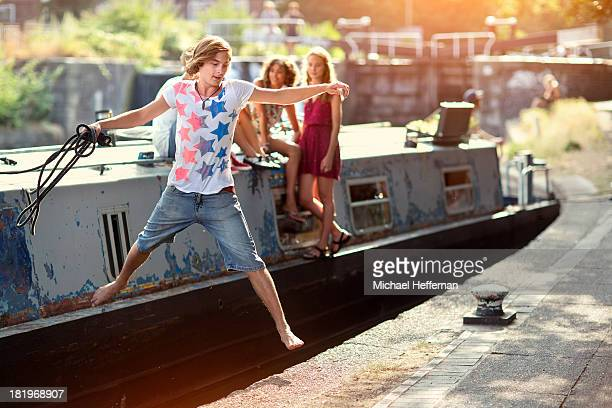 Young man jumping off canal boat