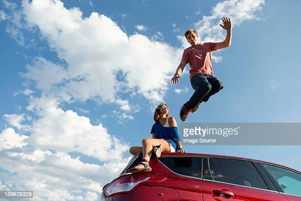 Young man jumping off car roof, girl sitting on roof
