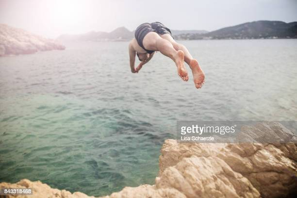 Young man jumping off cliff into water
