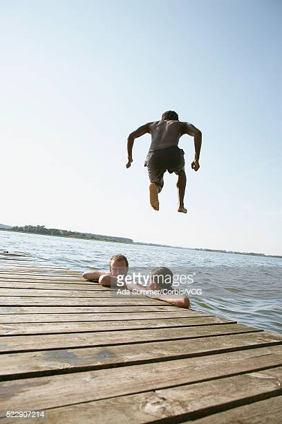 Young man jumping off dock
