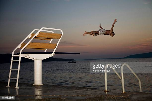 Young man jumping off of a diving board