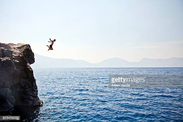 young man jumping off of cliff into crater lake on sunny day, crater lake national park, oregon, usa - rocha imagens e fotografias de stock