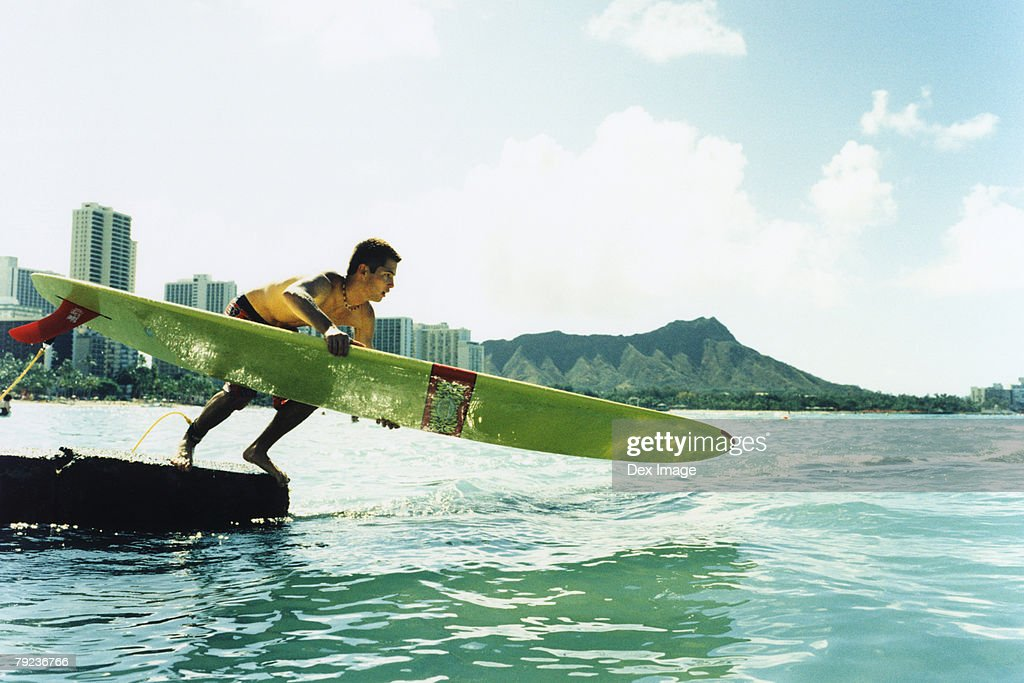 Young man jumping off with surfboard : Stock Photo