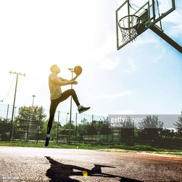 young man jumping on basketball court - making a basket scoring stock pictures, royalty-free photos & images
