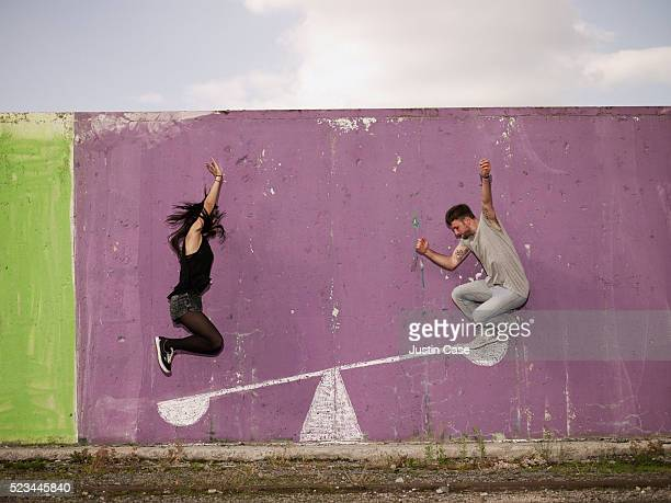 young man jumping on painted seesaw to push young woman up - seesaw stock pictures, royalty-free photos & images