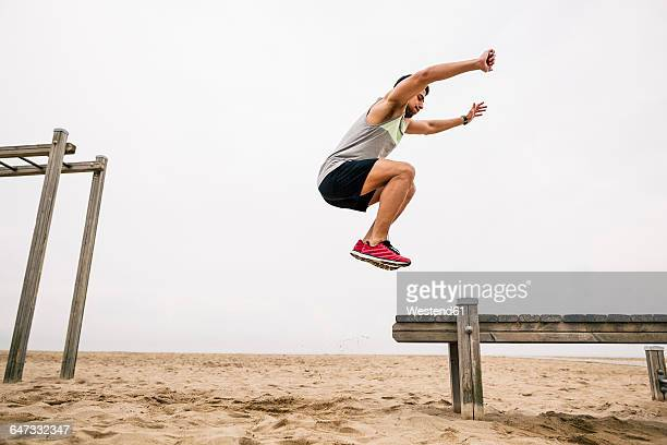 young man jumping on the beach - long jump stock pictures, royalty-free photos & images