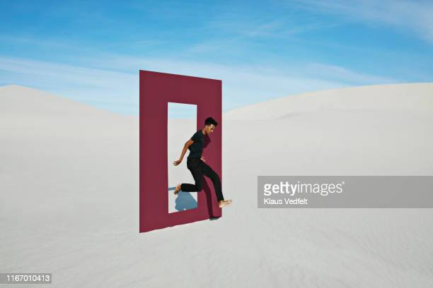 young man jumping on white sand through door frame at desert - day stock pictures, royalty-free photos & images